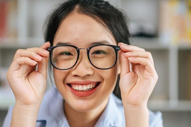 Protrait młoda azjatycka kobieta szczęśliwy pozytywny uśmiech i używa okularów dotykowych dłoni i patrząc na kamerę w salonie