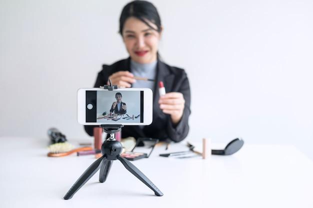 Prowadząc działalność online w mediach społecznościowych, piękna kobieta blogerka prezentuje obecny samouczek kosmetyczny i transmituje na żywo wideo do sieci społecznościowej podczas nagrywania nauczania