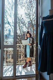 Prowadzenie spraw biznesowych. skoncentrowana kobieta w niebieskiej sukience i płaszczu, siedząca na środku balkonu i niosąca laptopa