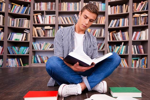 Prowadzi badania w bibliotece. skoncentrowany młody człowiek czyta książkę siedząc przy półce z książkami