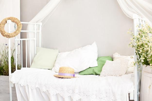 Prowansja w stylu rustykalnym. beczka z wazonami z białymi kwiatami stokrotki w jasnym, przytulnym wnętrzu sypialni. biała ściana, łóżko retro, słomkowy kapelusz. shabby chic wnętrze sypialni w stylu prowansalskim. wieś, dworek.