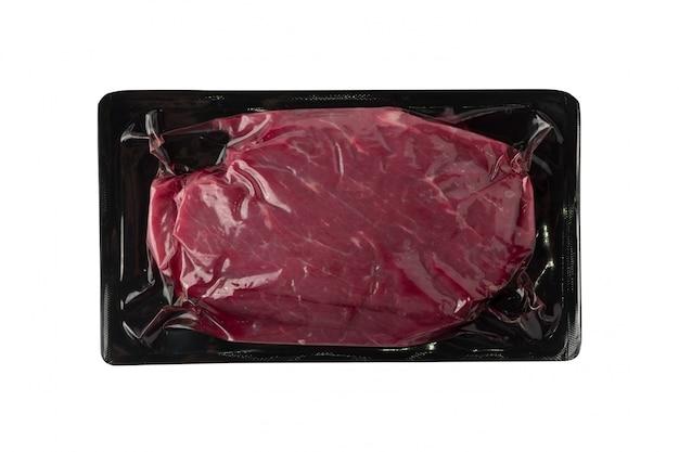 Próżniowe czarne plastikowe opakowanie ze świeżym stekiem wołowym na białym tle.