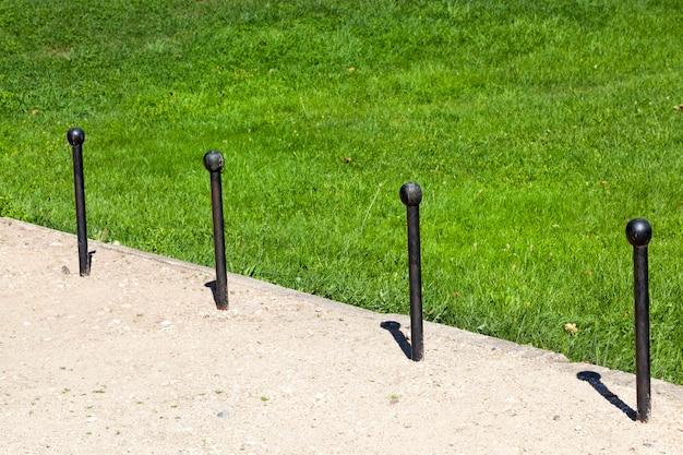 Prymitywne metalowe ograniczniki ruchu z czarnymi drewnianymi gałkami