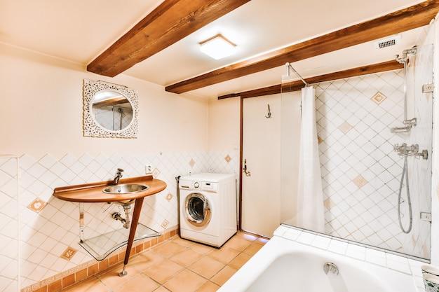 Prysznic i wanna w jasnej łazience z pralką i drewnianym stołem z umywalką pod drewnianymi belkami