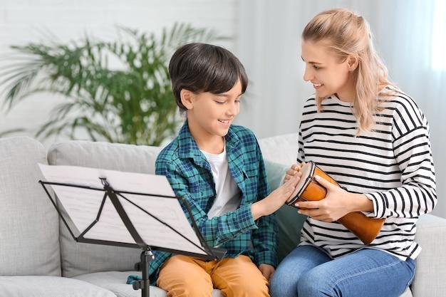 Prywatna nauczycielka muzyki udzielająca lekcji małemu chłopcu w domu