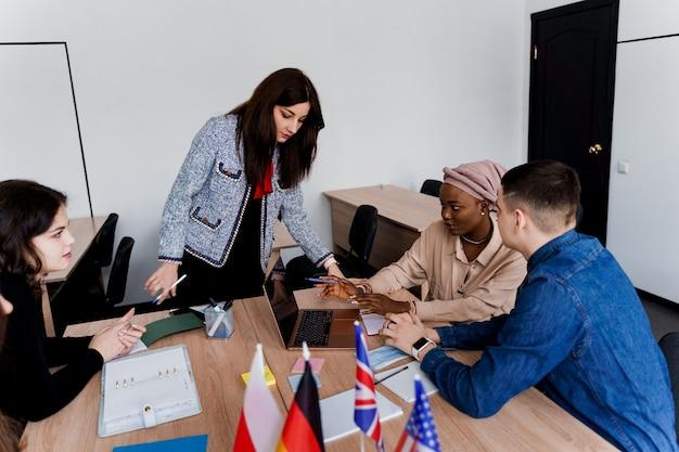Prywatna nauka w zagranicznej szkole z uczennicą. nauczyciel wyjaśnia gramatykę języka ojczystego na laptopie. przygotowanie do egzaminu z korepetytorem. z przodu flagi anglii, wielkiej brytanii, niemiec i polski.