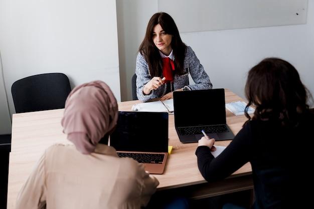 Prywatna nauka w zagranicznej szkole z uczennicą. nauczyciel wyjaśnia gramatykę języka ojczystego na laptopie. przygotowanie do egzaminu z korepetytorem.