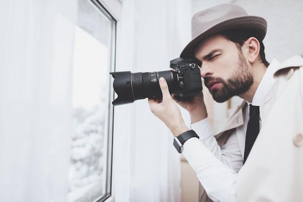 Prywatny detektyw robi zdjęcia w oknie.