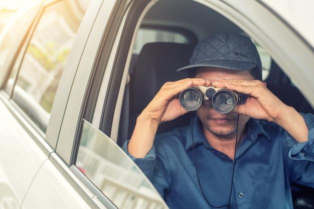 Prywatny detektyw siedzący wewnątrz samochodu fotografowanie aparatem slr