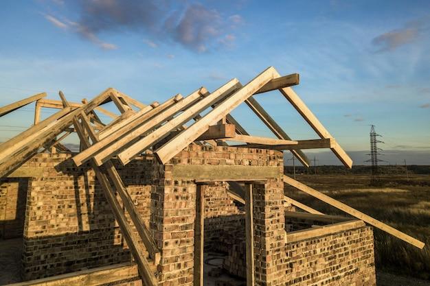 Prywatny dom mieszkalny z drewnianą konstrukcją ramy dachu w budowie. niedokończony budynek z cegły w budowie.