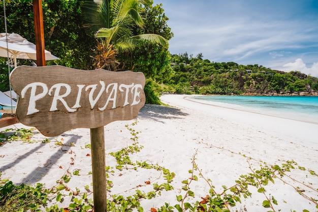 Prywatny znak na tropikalnej piaszczystej plaży z błękitną laguną oceaniczną na wyspie mahe na seszelach.