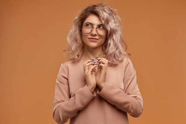 Przebiegła hipsterka planująca żart lub złą sztuczkę, ściskająca ręce i tajemniczo uśmiechająca się. zamyślona, przebiegła młoda kobieta w okularach, mająca podstępny plan