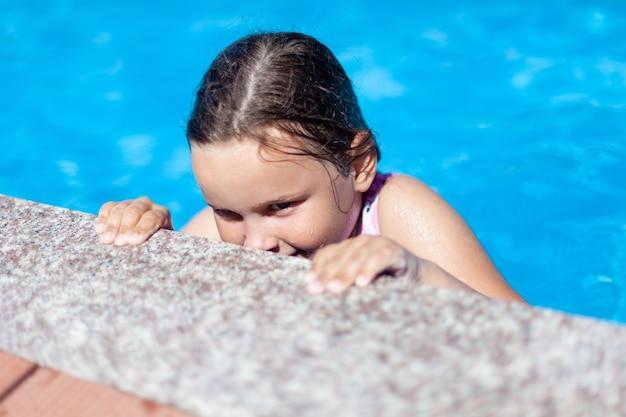 Przebiegła psotna dziewczyna wygląda zza krawędzi basenu i bawi się w szpiegów w hotelu na s...