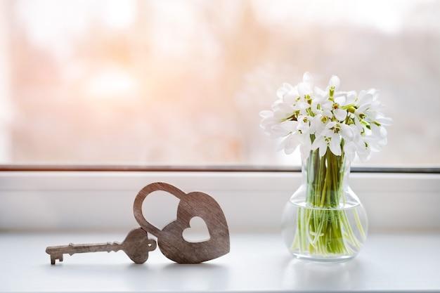 Przebiśniegi w wazonie przy oknie z ozdobnym zamkiem w kształcie serca. klimatyczna i romantyczna kompozycja na gratulacje z okazji walentynek. wolne miejsce na tekst