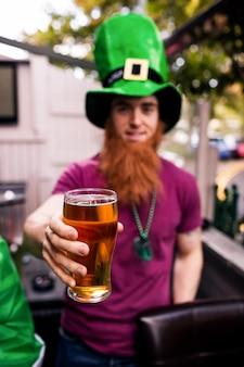 Przebrany mężczyzna trzyma kufel piwa
