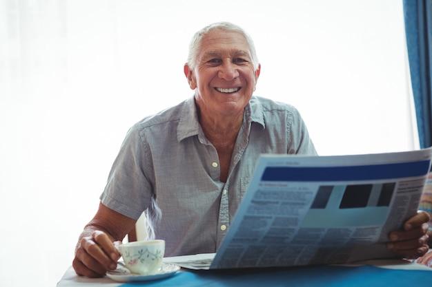 Przechodzić na emeryturę uśmiechnięty mężczyzna patrzeje kamerę