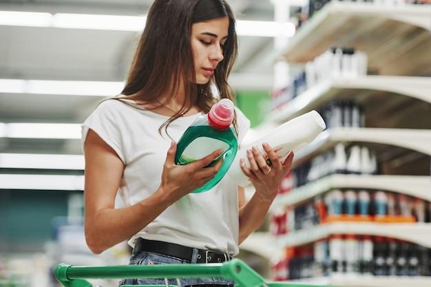 Przechowuje produkt. kobieta shopper w ubranie na rynku.