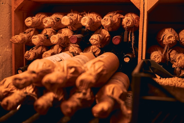 Przechowywanie napojów alkoholowych. rzędy butelek wina owiniętych w papier rzemieślniczy leżących na półkach