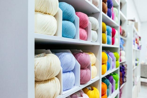 Przechowywanie różnych przędz wełnianych zorganizowanych według koloru na półce