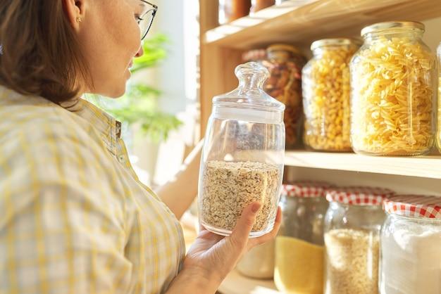 Przechowywanie żywności w spiżarni, kobieta trzyma w ręku słoik płatków owsianych
