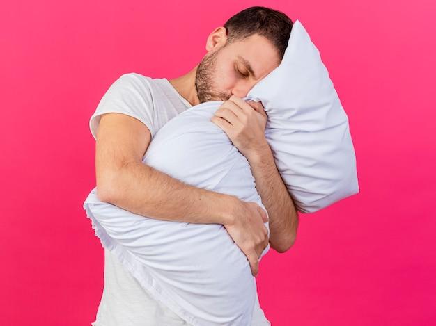 Przechylanie głowy młody chory przytulił poduszkę na różowym tle