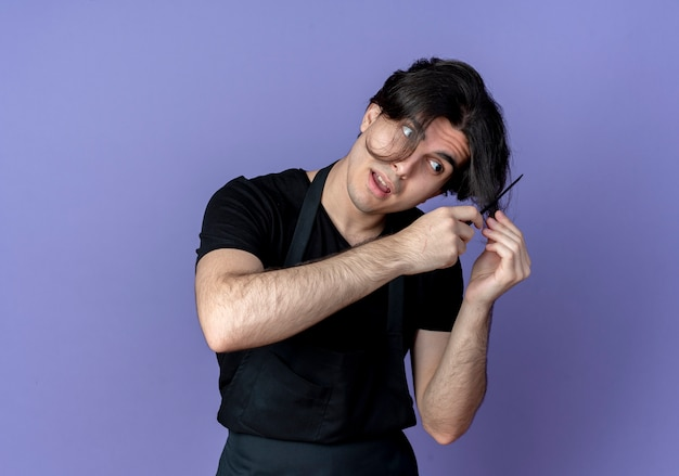 Przechylanie głowy młody przystojny mężczyzna fryzjer w mundurze czesanie włosów na niebieskim tle
