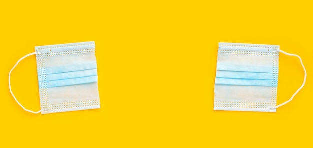 Przeciąć na pół twarzy ochronną maseczkę medyczną na żółtym tle.