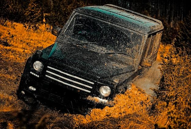 Przeciągnij samochód wyścigowy pali gumę z drogi podróż na górskiej drodze na błocie x offroad suv exp...