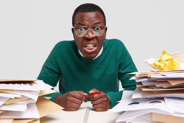 Przeciążony, zirytowany, ciemnoskóry pracownik, zajęty zbyt dużą ilością pracy, otoczony stosami papierów, notatek do projektu, trzyma pióro, siedzi przy biurku