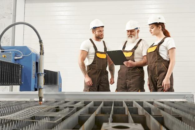 Przecinarka plazmowa i trzej inżynierowie rozmawiają, patrząc na folder