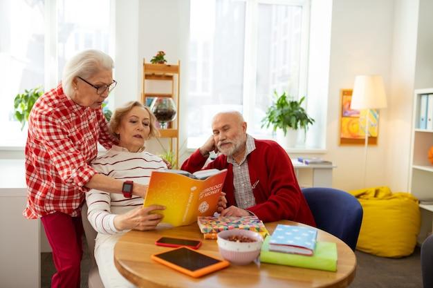 Przeczytaj tutaj. przyjemna starsza kobieta wskazująca na książkę, stojąc za swoim przyjacielem