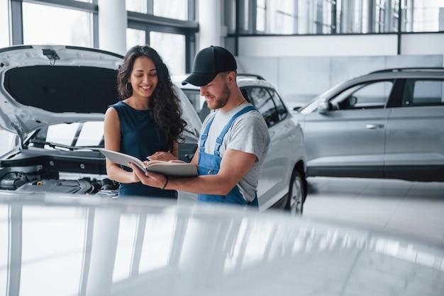 Przeczytaj uważnie. kobieta w salonie samochodowym z pracownikiem w niebieskim mundurze, odbierając naprawiony samochód