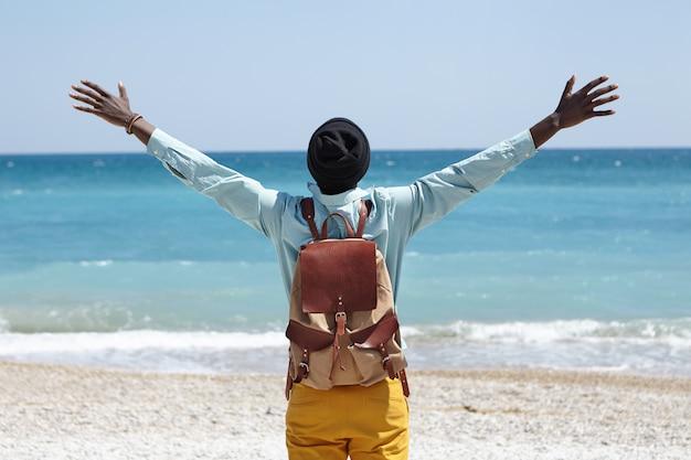 Przeczytaj widok szczęśliwego, beztroskiego mężczyzny afroamerykanina stojącego na plaży nad lazurowym morzem, rozkładającego ramiona, czującego wolność i połączenie z otaczającą go niesamowitą przyrodą