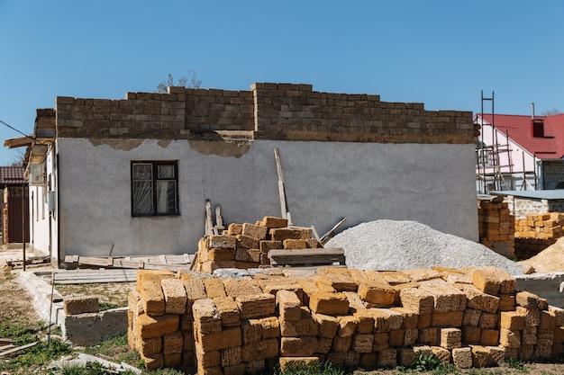 Przed budującym się domem leży stos cegieł