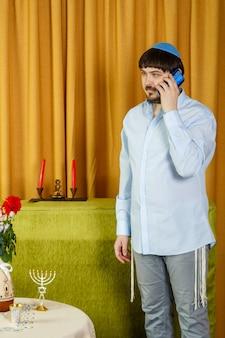Przed ceremonią chupy pan młody w synagodze, czekając na pannę młodą, rozmawia przez telefon. zdjęcie pionowe