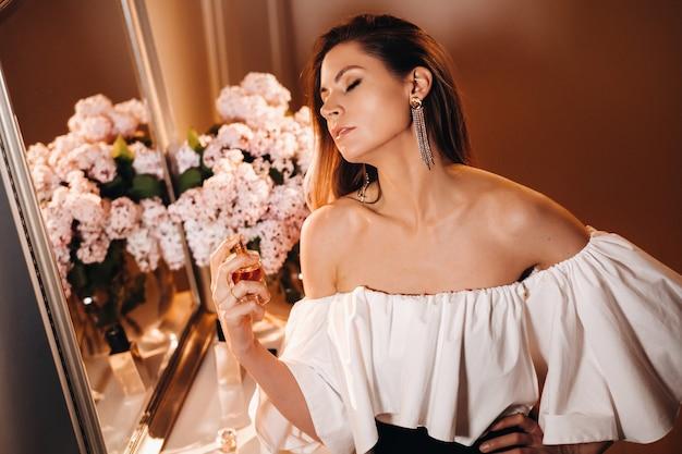 Przed domową toaletką stoi młoda kobieta w wieczorowej sukni z perfumami, która przed wyjściem na imprezę używa perfum.