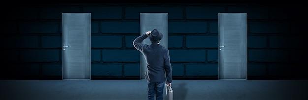 Przed drzwiami stoi mężczyzna w kapeluszu