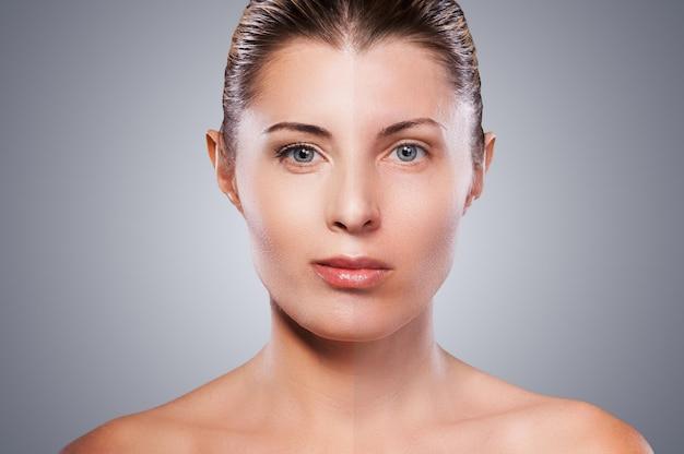 Przed i po. portret pięknej dojrzałej kobiety z makijażem pół twarzy stojącej na szarym tle