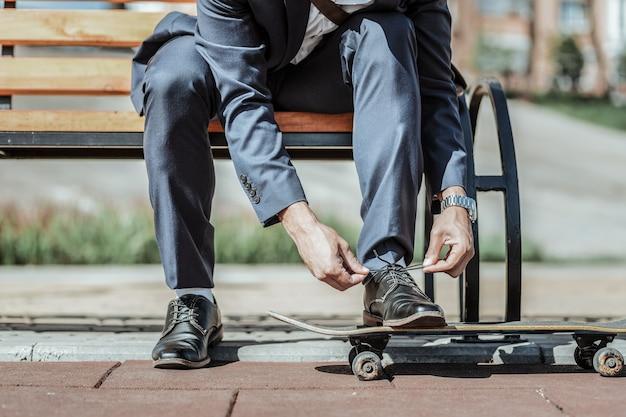 Przed jazdą na deskorolce. zbliżenie na atrakcyjne męskie dłonie wiązanie sznurówek i przygotowanie do jazdy na deskorolce