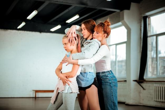 Przed lustrem. rudowłosa młoda nauczycielka tańca i jej uczniowie zamyśleni stojąc przed lustrem