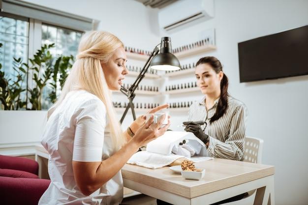 Przed manicure. blond włosa bizneswoman pije herbatę przed manicure w swoim ulubionym salonie piękności