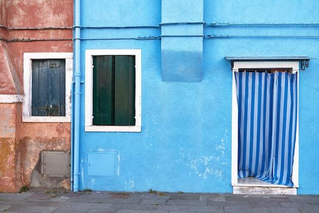 Przed niebieskim domem na wyspie burano. włochy, wenecja