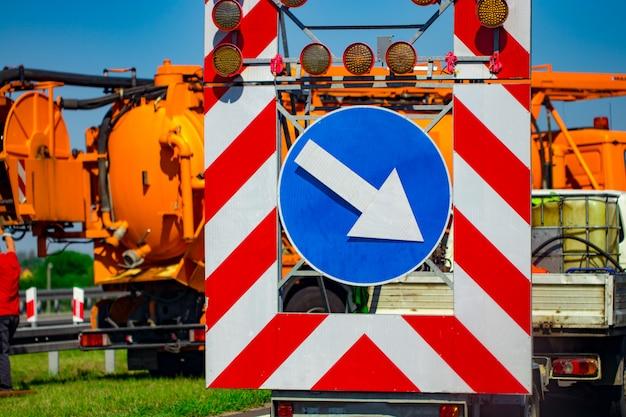 Przed nimi biegnie znak ostrzegawczy na drodze. znak drogowy. naprawa dróg.