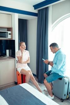 Przed opuszczeniem. rozważni mąż i żona siedzący na swoich walizkach podróżnych w domu zamawiający za pomocą smartfonów taksówkę na lotnisko.
