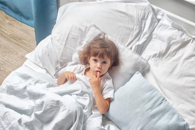 Przed snem dziecko leży w wygodnym łóżku. dobry sen dla dziecka i dobranoc.