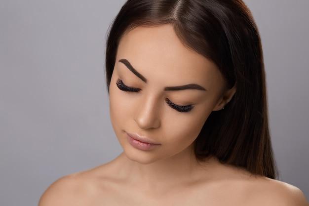 Przedłużanie rzęs, sztuczne rzęsy, portret seksownej dziewczyny z długimi sztucznymi rzęsami i perfekcyjnym makijażem,