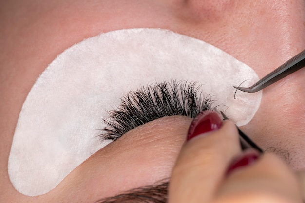 Przedłużanie rzęs. sztuczne rzęsy. procedura przedłużania rzęs. zamknij się portret kobiety oko z długimi rzęsami. profesjonalna stylistka wydłużająca kobiece rzęsy. mistrz i klient w salonie kosmetycznym.