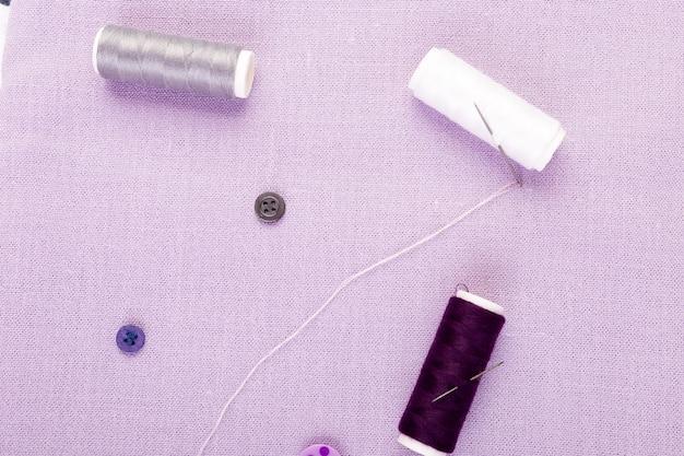 Przedmioty do szycia ubrań. guziki do szycia, szpule nici i tkaniny. widok z góry.