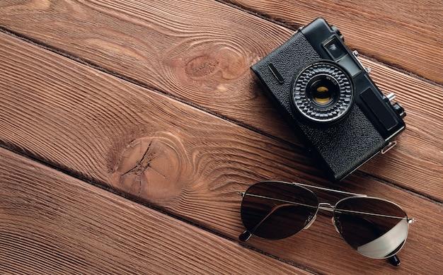 Przedmioty na wakacje: aparat fotograficzny, okulary przeciwsłoneczne. akcesoria podróżnicze na drewnianym tle. zestaw turystyczny układu fotografa ulicznego.