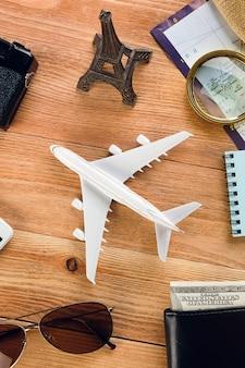 Przedmioty na wakacje: aparat fotograficzny, okulary przeciwsłoneczne, pieniądze w portfelu, słomkowy kapelusz i telefon komórkowy. plan podróży, akcesoria podróżne na drewnianej powierzchni. układ turystyczny - zestaw podróżnika.